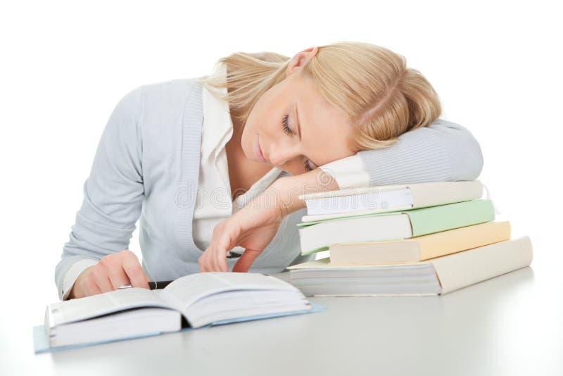 Mooi studentenmeisje dat van het doen van thuiswerk wordt vermoeid stock afbeeldingen