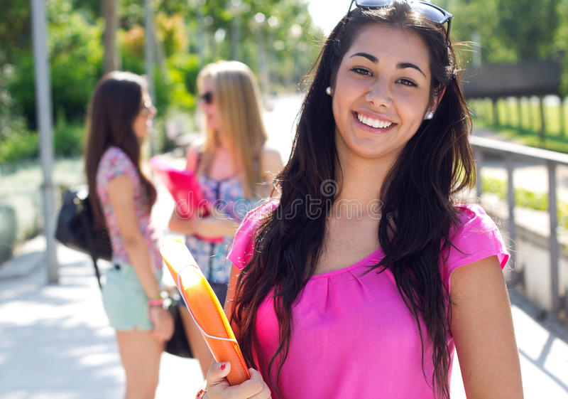 Mooi studentenmeisje met sommige vrienden na school stock foto's