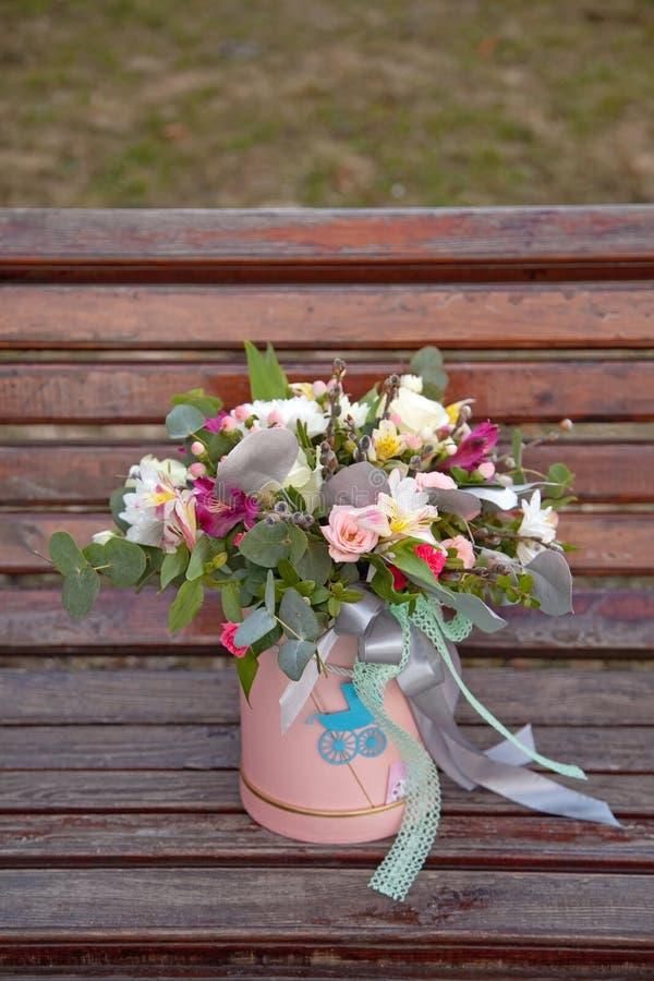 Mooi teder boeket van bloemen in roze doos op houten backgr royalty-vrije stock foto