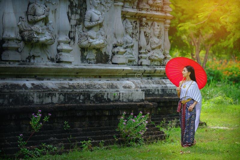 Mooi Thais meisje in de traditionele rode paraplu van het kledingskostuum zoals stock afbeelding
