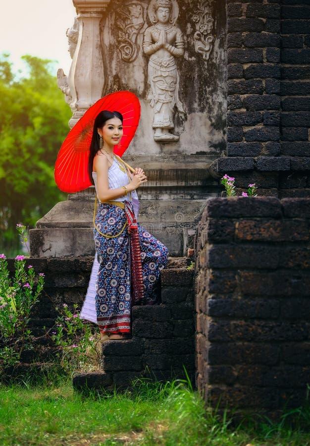 Mooi Thais meisje in de traditionele rode paraplu van het kledingskostuum zoals stock afbeeldingen