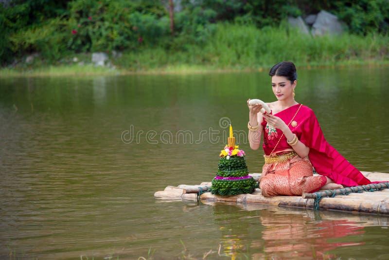 Mooi Thais meisje die rode Thaise traditionele kleding in Loy Krathong-festival dragen stock afbeeldingen