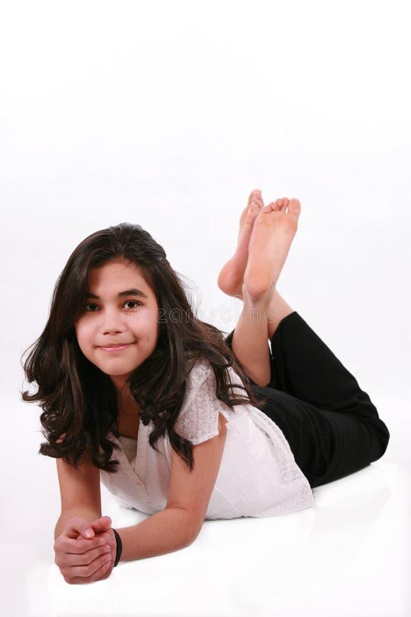 Mooi tienermeisje dat bij vloer het ontspannen ligt stock foto
