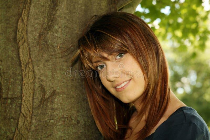 Mooi tienermeisje dat op boom leunt stock afbeeldingen
