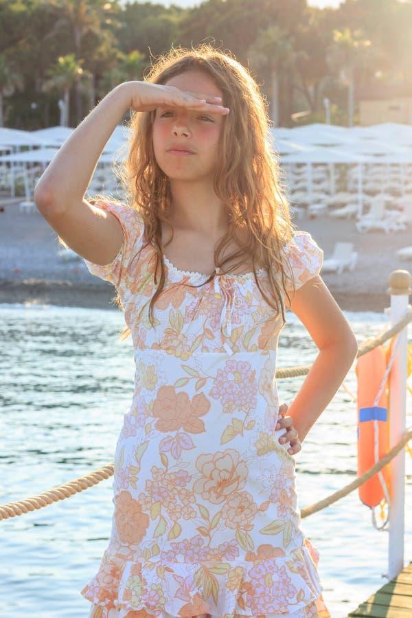 Mooi tienermeisje in de stralen van de het plaatsen zon op een pijler door het overzees stock afbeelding