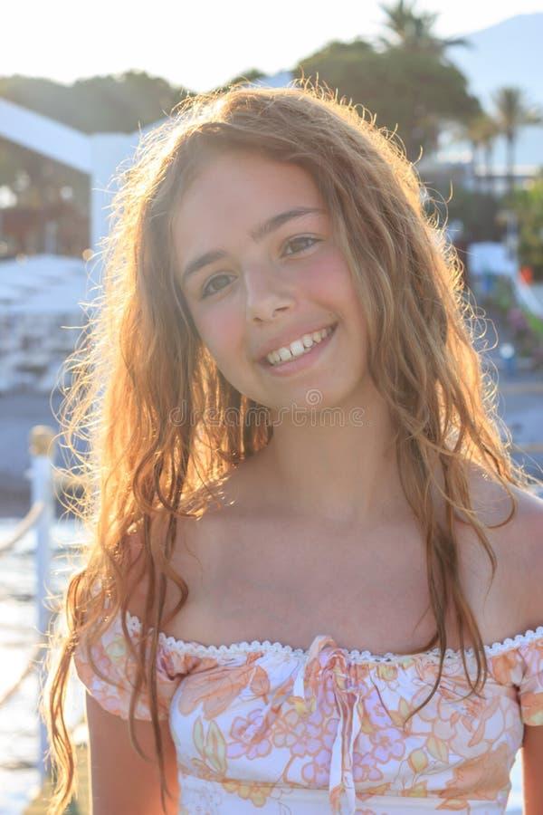 Mooi tienermeisje in de stralen van de het plaatsen zon op een pijler door het overzees royalty-vrije stock afbeelding