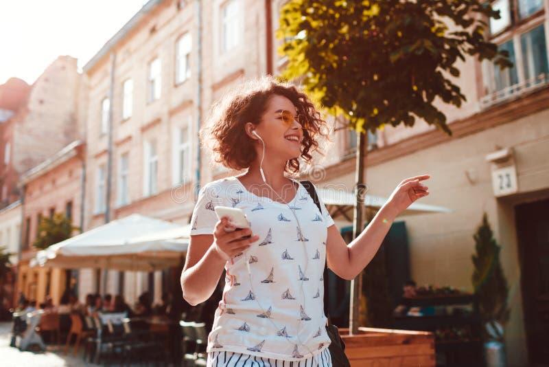 Mooi tienermeisje die aan de muziek luisteren die langs oude stad straten en het dansen lopen stock afbeelding