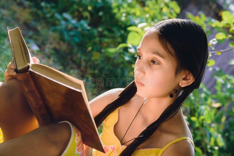 Mooi tienermeisje die een boek in de tuin lezen stock foto