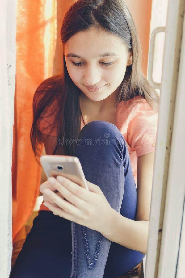 Mooi tienermeisje die een mobiele telefoon houden Levensstijlstijl stock afbeelding