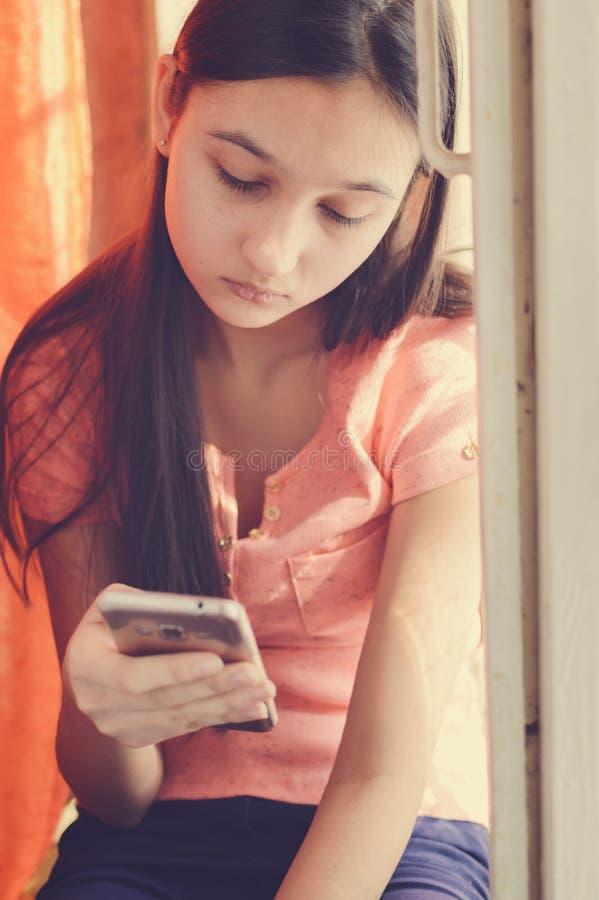 Mooi tienermeisje die een mobiele telefoon houden Levensstijlstijl royalty-vrije stock foto's