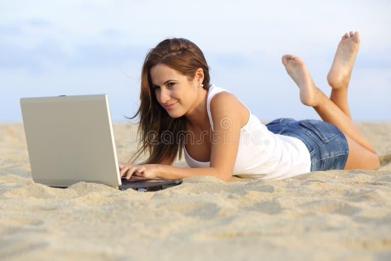 Mooi tienermeisje die haar laptop doorbladeren die op het zand van het strand liggen royalty-vrije stock afbeelding