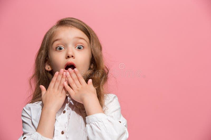 Mooi tienermeisje die verrast geïsoleerd op roze kijken stock afbeelding