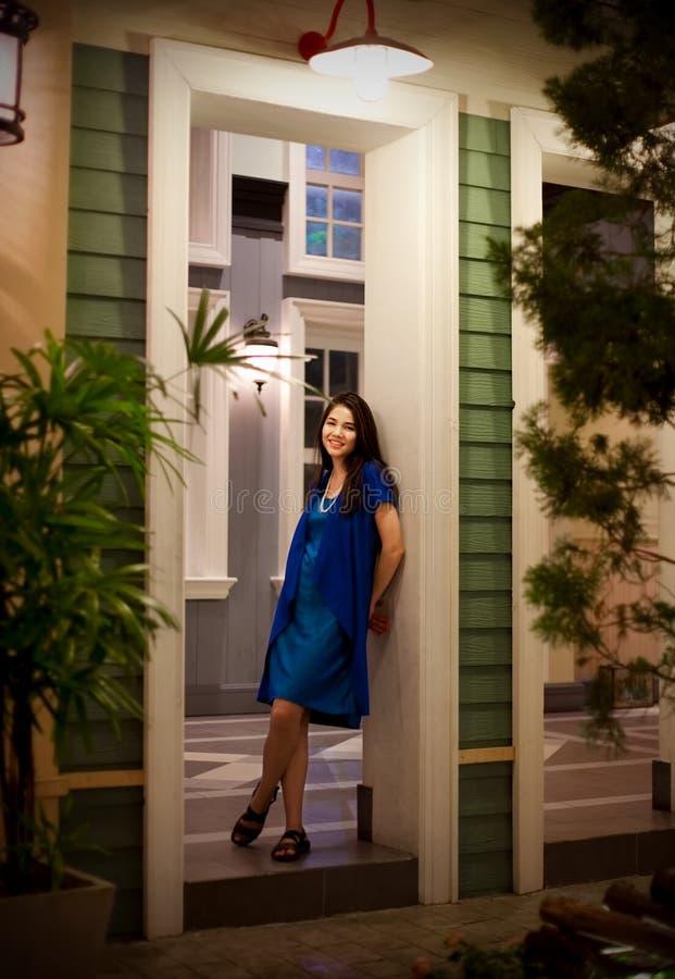 Mooi tienermeisje die zich in deuropening in avond bevinden royalty-vrije stock fotografie