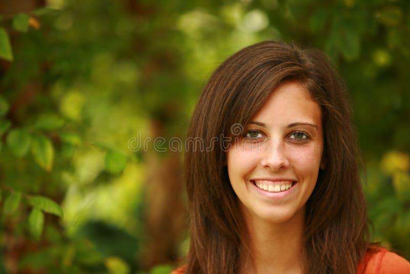 Mooi tienermeisje door bladeren stock foto
