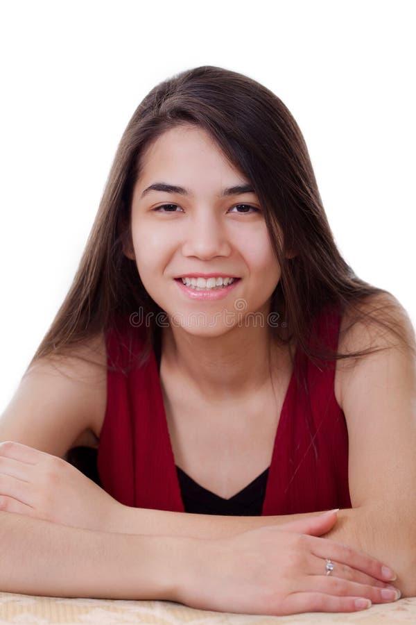 Mooi tienermeisje in het rode kleding glimlachen, die camera onder ogen zien stock afbeeldingen