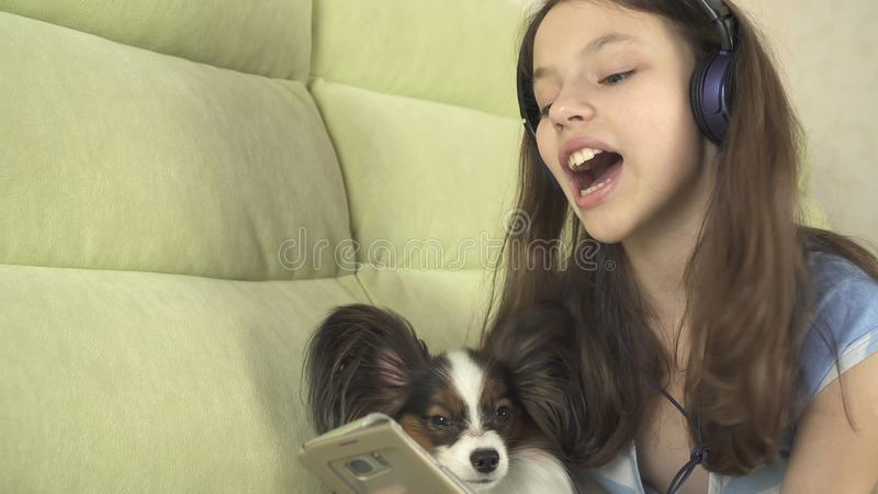 Mooi tienermeisje in hoofdtelefoons die karaokeliederen in smartphone met hond zingen royalty-vrije stock afbeelding