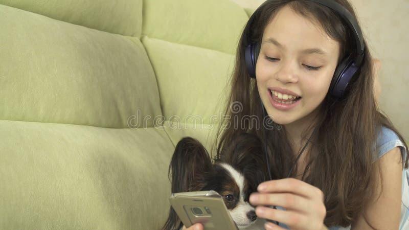 Mooi tienermeisje in hoofdtelefoons die karaokeliederen in smartphone met hond zingen royalty-vrije stock afbeeldingen