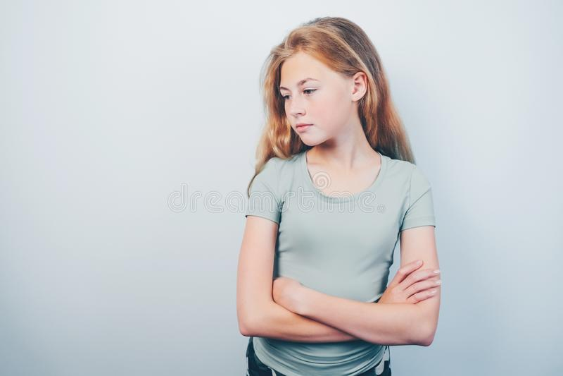 Mooi tienermeisje met gekruiste wapens die zich tegen grijze achtergrond bevinden royalty-vrije stock afbeelding