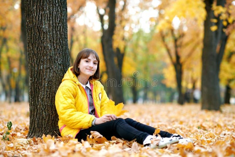 Mooi tienermeisje met gele bladeren die in het park van de de herfststad stellen Zij zit onder de boom royalty-vrije stock fotografie