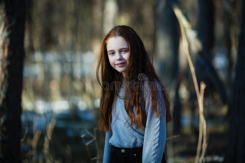 Mooi tienermeisje met het lange haar stellen voor een portret in een pijnboombos stock foto's