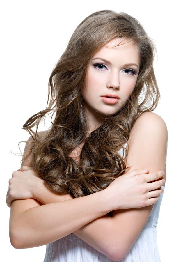 Mooi tienermeisje met lange krullende haren stock afbeelding