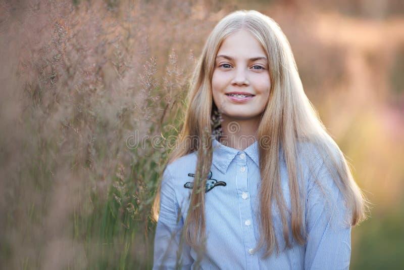 Mooi tienermeisje met steunen bij haar tanden het glimlachen stock afbeelding