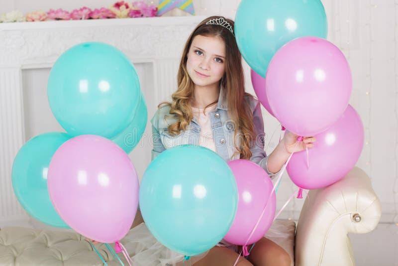 Mooi tienermeisje met vele blauwe en roze ballons stock afbeelding