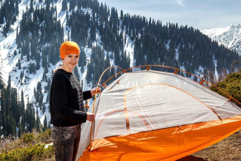 Mooi toeristenmeisje die zich dichtbij een tent op een achtergrond van bos snow-capped bergen bevinden stock fotografie
