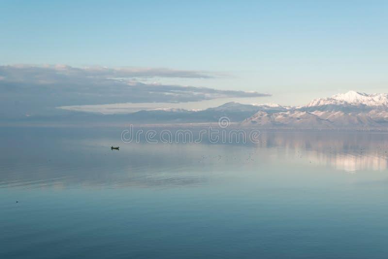 Mooi toneellandschap van Shkodra-meer, bergenbezinning en een weinig vissersboot stock fotografie