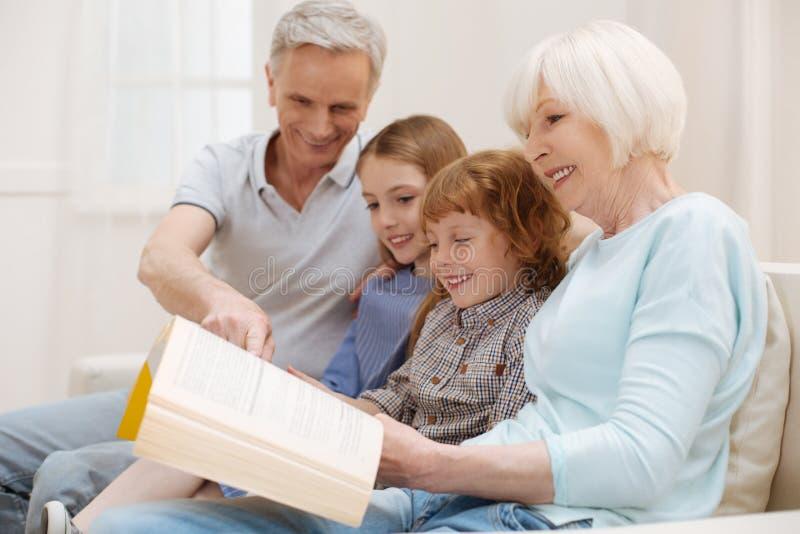 Mooi trillend paar die van goed verhaal met kleinkinderen genieten stock foto's