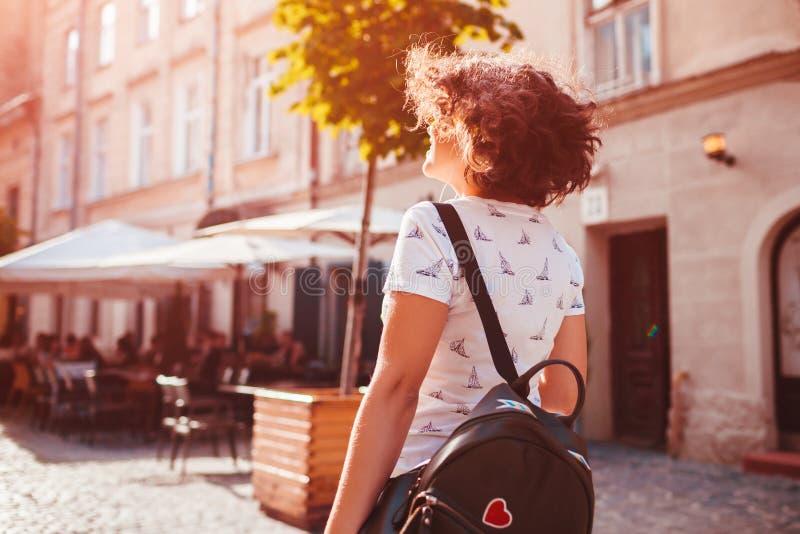 Mooi universiteitsmeisje die op de zomerstraat lopen Jonge vrouw met rugzak het koelen tijdens vakantie stock fotografie