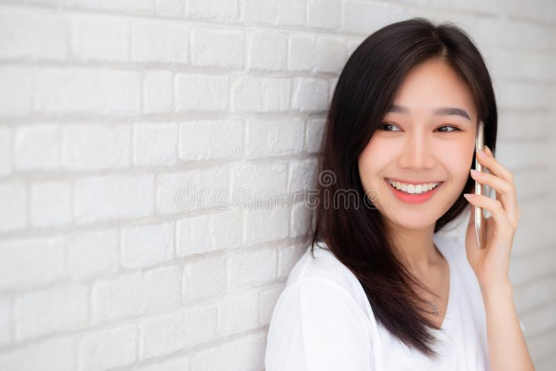 Mooi van de besprekings slimme telefoon en glimlach die van de portret jonge Aziatische vrouw zich op de achtergrond van de cemen stock fotografie