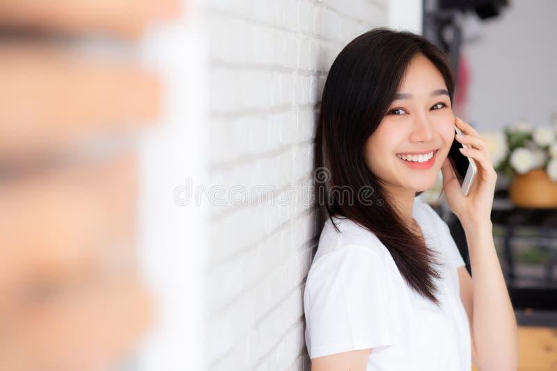 Mooi van de besprekingssmartphone en glimlach die van de portret jonge Aziatische vrouw zich op de achtergrond van de cementbakst royalty-vrije stock fotografie