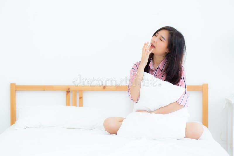 Mooi van de geeuwzitting van de portret jonge Aziatische vrouw met slaap op bed bij slaapkamer royalty-vrije stock afbeelding