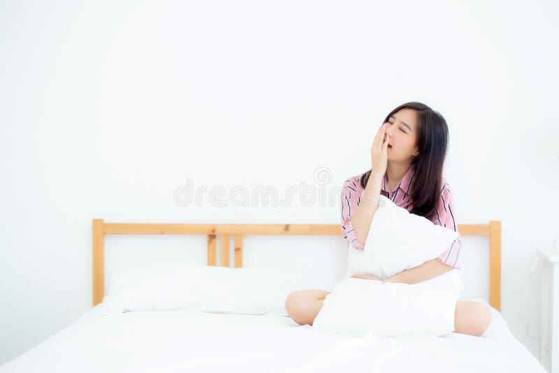 Mooi van de geeuwzitting van de portret jonge Aziatische vrouw met slaap op bed bij slaapkamer royalty-vrije stock foto