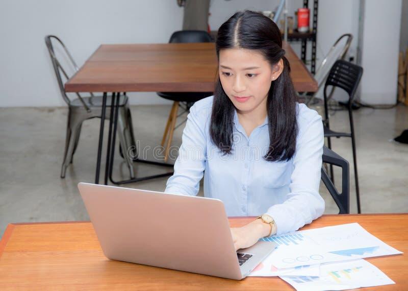 Mooi van portret het Aziatische jonge vrouw werken met het document van de grafiekstatistiek aan laptop zitting bij koffiewinkel royalty-vrije stock afbeelding