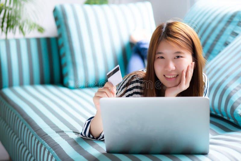 Mooi van portret jonge Aziatische vrouw het liggen gebruikerscreditcard met laptop, Tevreden meisje die online winkelen royalty-vrije stock afbeeldingen