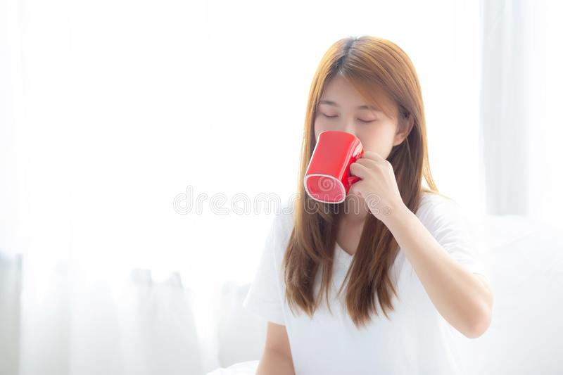 Mooi van portret jonge Aziatische vrouw met drank een kop van het vensterachtergrond van het koffie bevindende gordijn stock foto