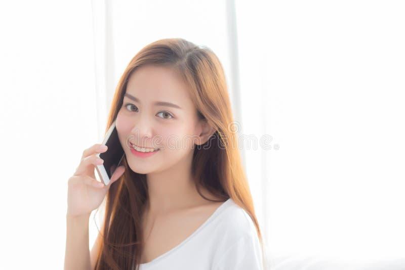 Mooi van portret jonge Aziatische vrouw slimme mobiele telefoon spreken en glimlach die zich bij gordijnachtergrond bevinden op s stock foto