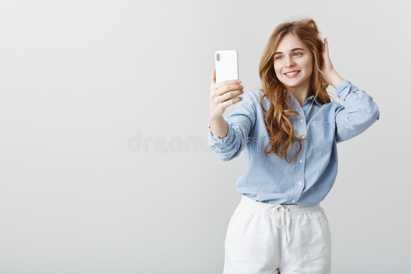 Mooi vandaag en zeker het voelen Portret van tevreden aantrekkelijke vrouwelijke vrouwelijke student in het blauwe blouse control royalty-vrije stock afbeelding