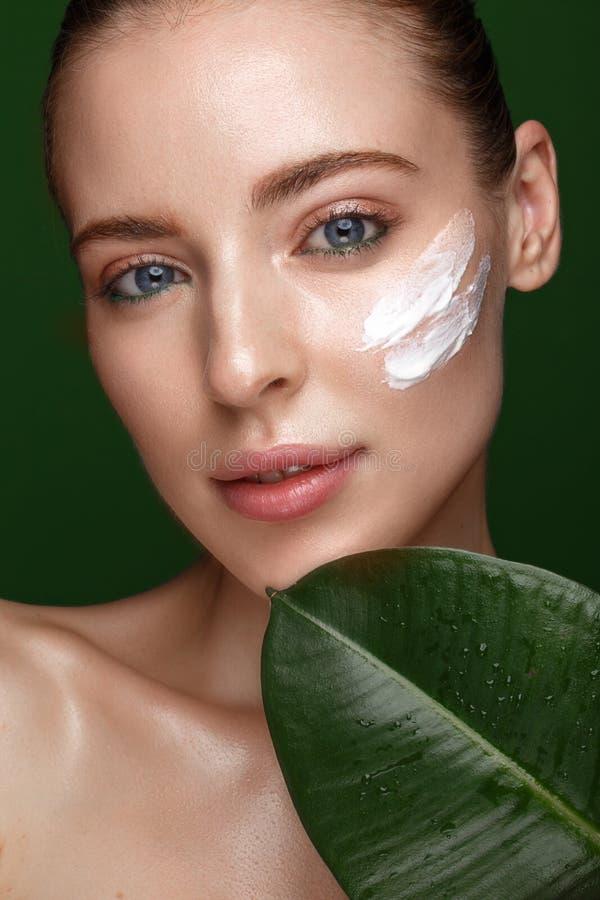 Mooi vers meisje met kosmetische room op het gezicht, de natuurlijke samenstelling en de groene bladeren Het Gezicht van de schoo royalty-vrije stock fotografie