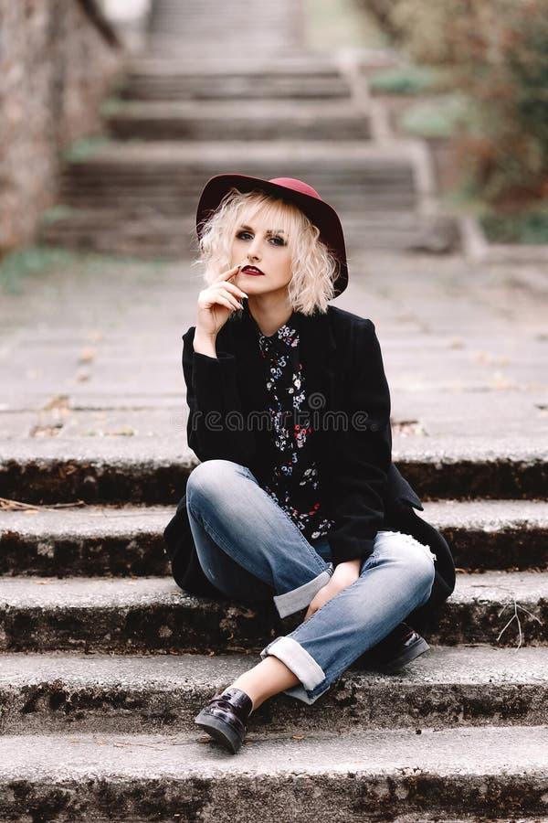 Mooi vrolijk blondemeisje met kort krullend haar in laag en hoedenzitting op treden op de straat stock afbeelding