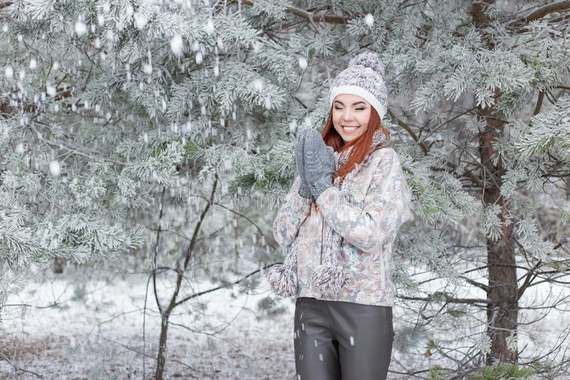 Mooi vrolijk gelukkig meisje met rood haar in een warme hoed en sjaal die en rond in de sneeuw in het de winterbos spelen een voo royalty-vrije stock foto's