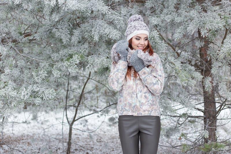 Mooi vrolijk gelukkig meisje met rood haar in een warme hoed en sjaal die en rond in de sneeuw in het de winterbos spelen een voo royalty-vrije stock fotografie