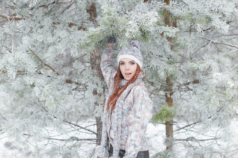 Mooi vrolijk gelukkig meisje met rood haar in een warme hoed en sjaal die en rond in de sneeuw in het de winterbos spelen een voo royalty-vrije stock afbeelding