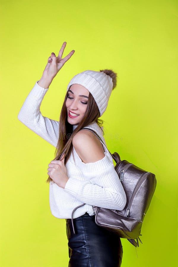 Mooi vrolijk meisje met een rugzak in een sweater op een heldere geïsoleerde achtergrond stock fotografie