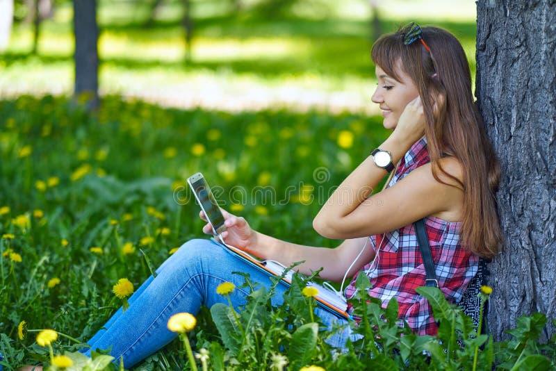 Mooi vrolijk meisje met een smartphonezitting in een park op een bank op een zonnige dayteenager, online het winkelen concept stock afbeeldingen