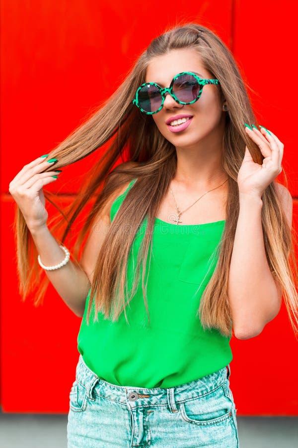Mooi vrolijk meisje in zonnebril op een heldere rode achtergrond royalty-vrije stock afbeeldingen