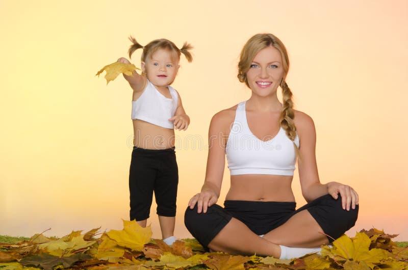 Mooi vrouw en kind die yoga in daling doen royalty-vrije stock afbeeldingen