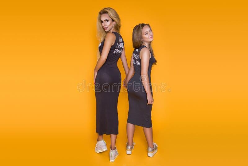 Mooi, vrouw, moeder met dochter, kleedde zich in dezelfde de zomerkleding, die op een gele achtergrond stellen stock foto's